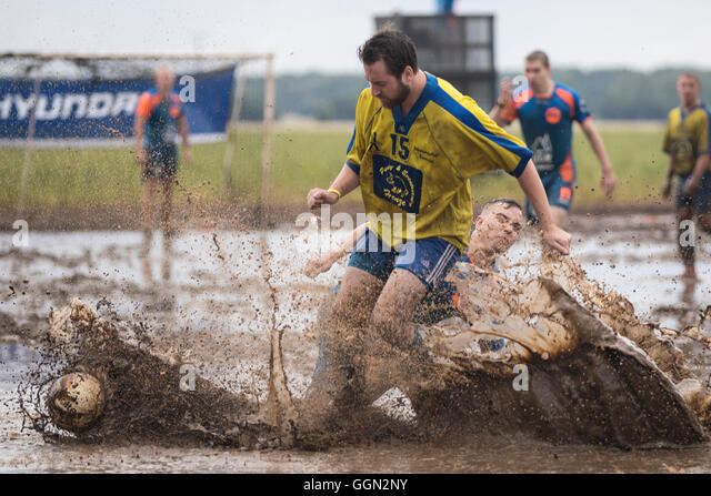 Woellnau, Germany. 06th Aug, 2016. Participants in the German Championship in Mud Soccer sink ankle-deep into a - Stock-Bilder