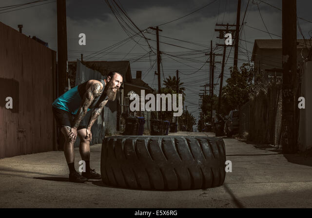 Mid adult man standing by large tire - Stock Image