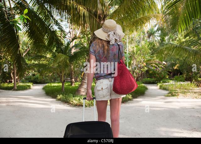 Woman rolling luggage in tropical resort - Stock-Bilder