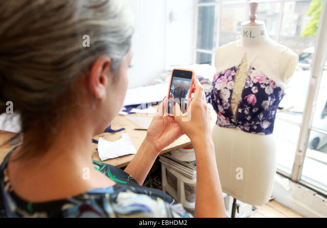 Designer taking photograph of her creation in studio - Stock Image