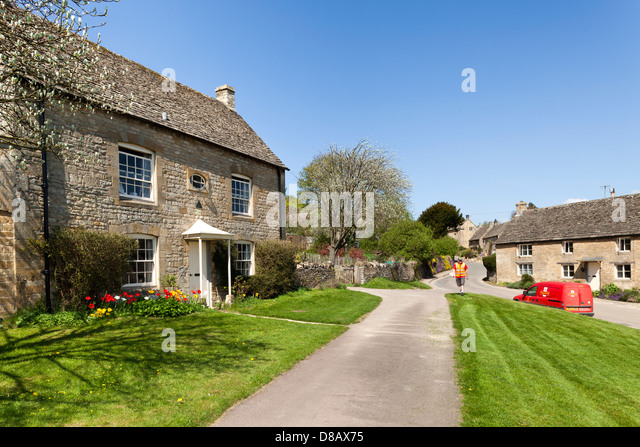 Royal Mail postman delivering mail in the Cotswold village of Guiting Power, Gloucestershire UK - Stock Image