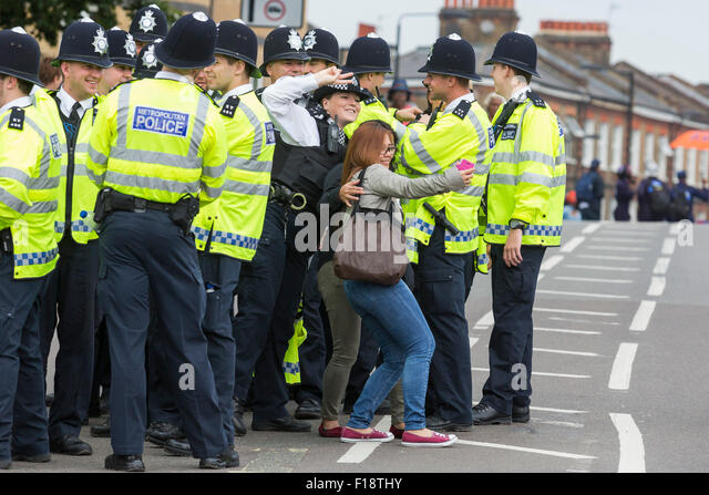 London, UK. 30 August 2015. A female police officer poses for a selfie with revellers. The Notting Hill Carnival - Stock Image