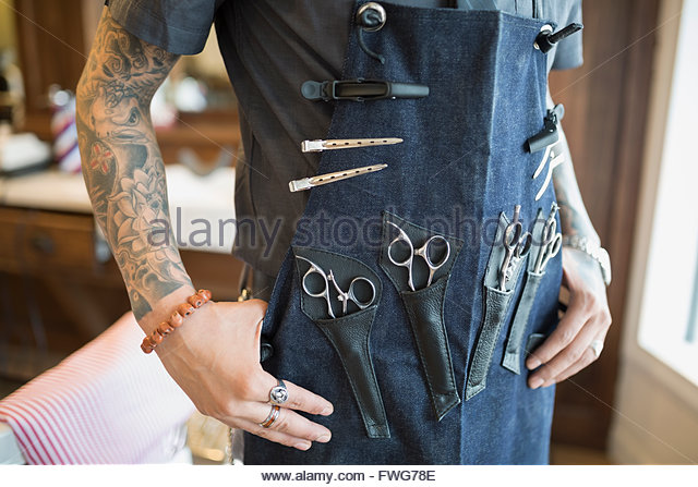 Midsection tattooed barber wearing apron with tools - Stock Image