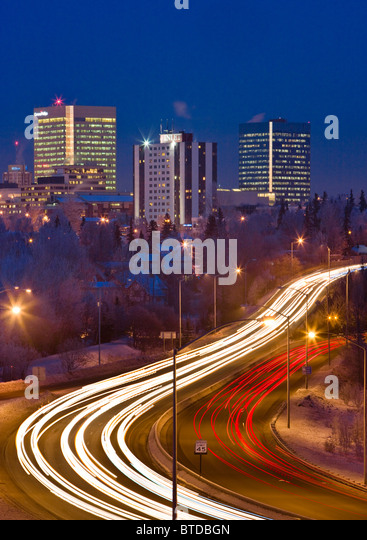 Twilight view of traffic on Minnesota Blvd. with downtown Anchorage in the background, Southcentral Alaska, Winter/n - Stock Image
