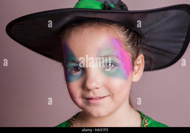 Little cute girl made up and costumed as a witch before halloween party. She is smiling - Stock Image
