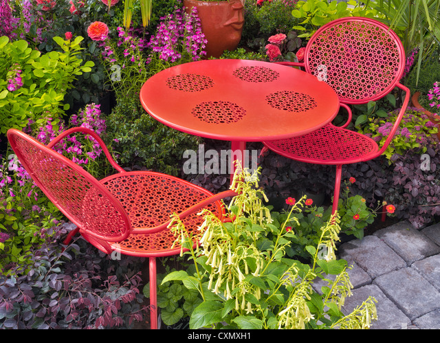 Table and chairs in flower garden display. Al's Nursery. Sherwood, Oregon - Stock Image