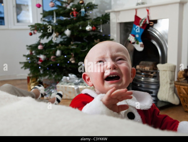 A baby crying at Christmas - Stock Image