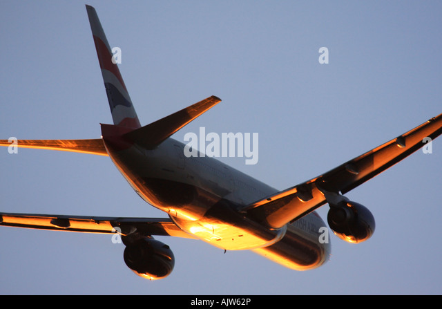 British Airways Boeing 777 just after take off in reflecting sunset light at Heathrow Airport, London, England, - Stock Image