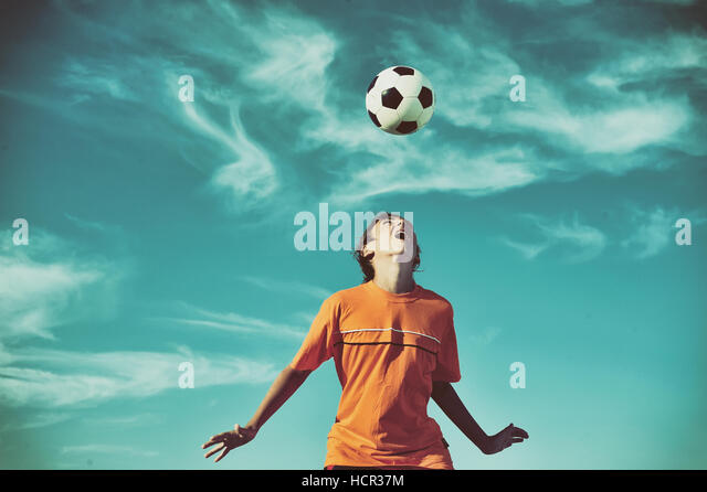 Young boy playing football - low angle virw - Stock Image