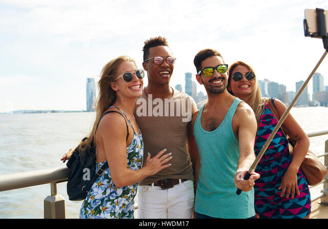 Four adult friends taking smartphone selfie on waterfront with skyline, New York, USA - Stock-Bilder