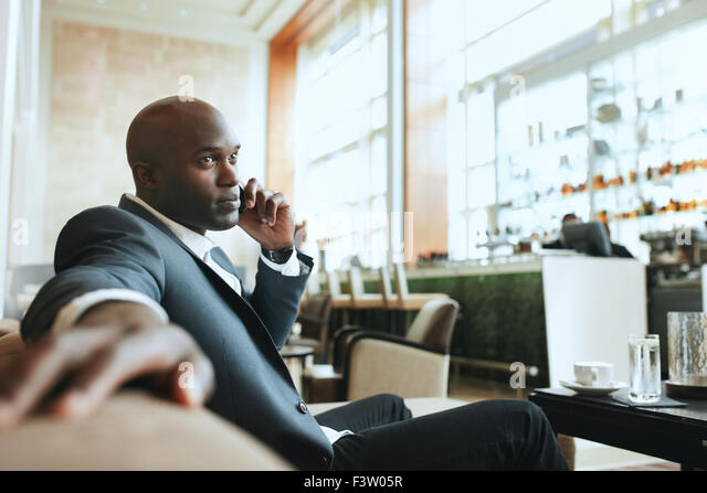African business man talking on mobile phone while waiting in a hotel lobby. Young business executive using cell - Stock-Bilder