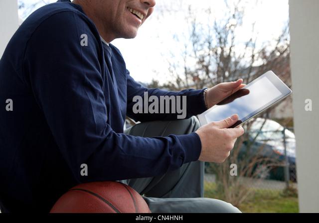 Mature man using digital tablet outdoors - Stock Image