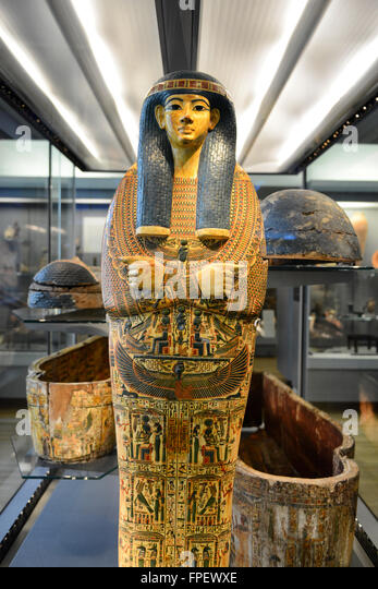 Egyptian Pharaoh Mummy Coffin Shrine Decorated in Ornate Hieroglyphics Standing Amongst Open Coffins in Museum Display - Stock Image