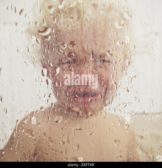 Boy standing in the shower crying - Stock Image