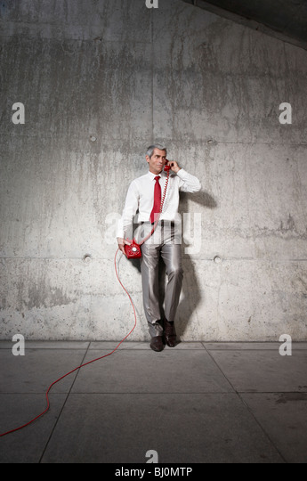 businessman talking on red telephone - Stock Image