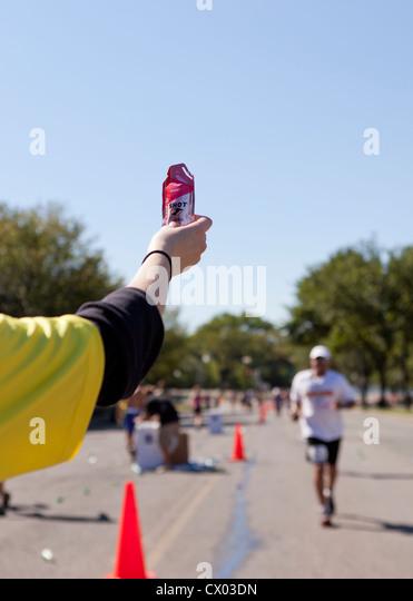 A marathon volunteer offering energy gel to runner - Stock Image