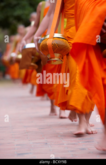 the procession of monks at dawn through the town to collect gifts of food, Luang Prabang, Laos - Stock Image