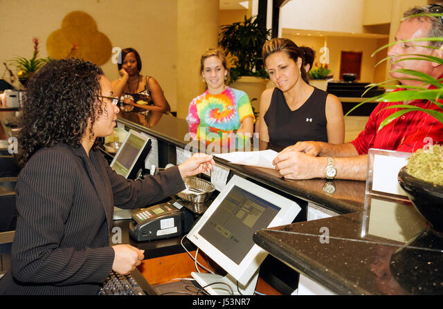 Little Rock Arkansas The Peabody Little Rock hotel Black woman man teen girl family desk clerk job public hospitality - Stock Image