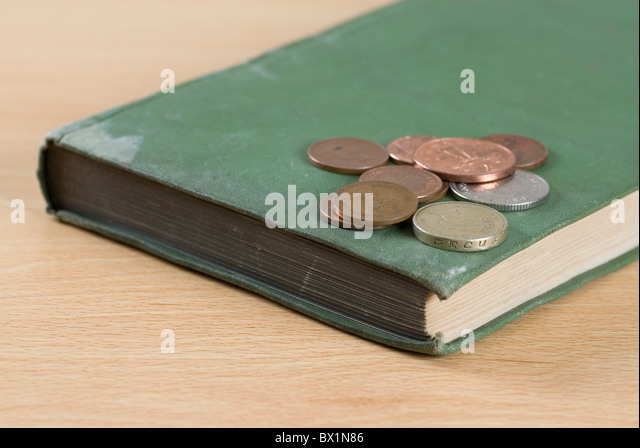 British coins over an old book - Stock Image
