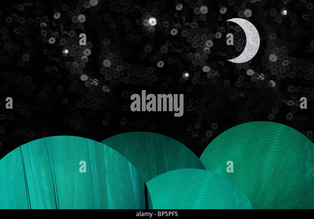 Green coloured hills at night with moon - Stock Image