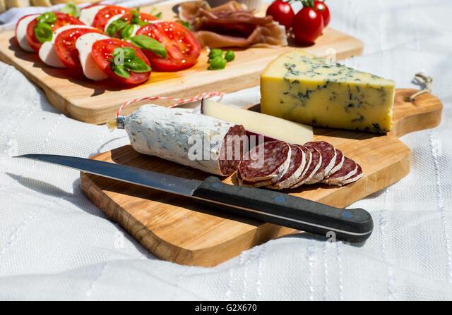 Close up of cut salami in a picnic of tomato and mozzarella salad, parma ham, strawberries, olives and espresso - Stock Image