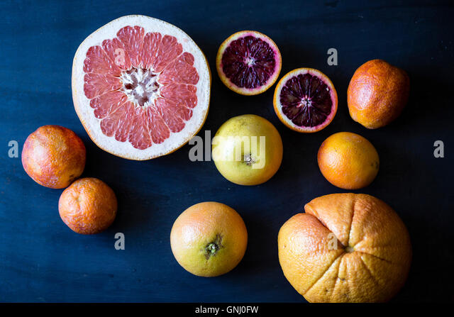 Citrus fruits and a blue background. Grapefruits, oranges, blood oranges. - Stock Image