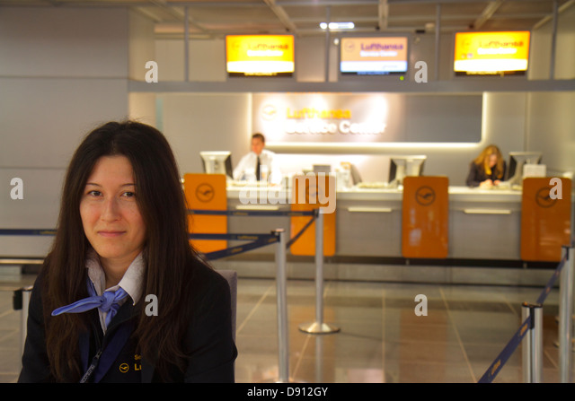 Germany Frankfurt am Main Airport FRA terminal gate area concourse Lufthansa service center centre woman employee - Stock Image