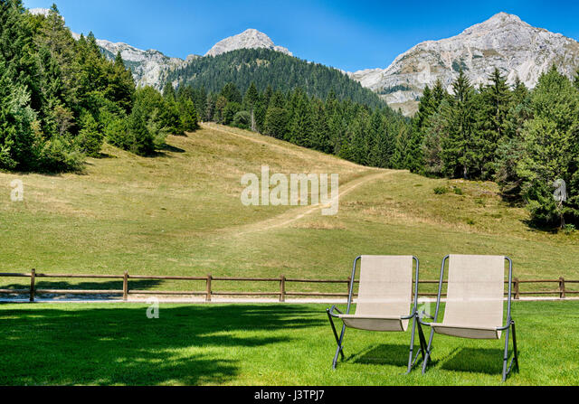 Two deck chairs on the meadow with panoramic mountain views in the background, Molveno - Stock Image