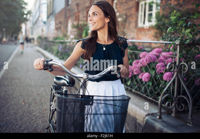Cheerful young woman looking away while walking down the street with a bike. Female with a bicycle on city road - Stock Image