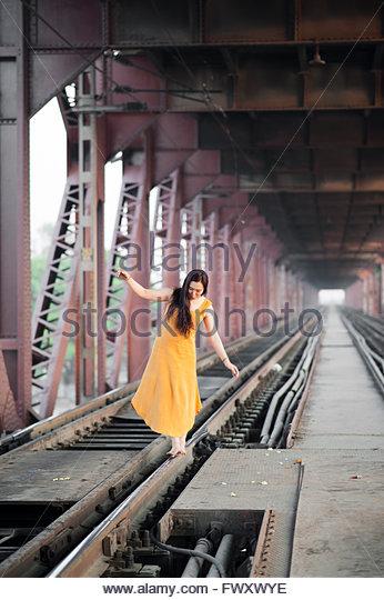 India, Uttar Pradesh, Varanasi, Young woman standing barefoot under bridge - Stock-Bilder