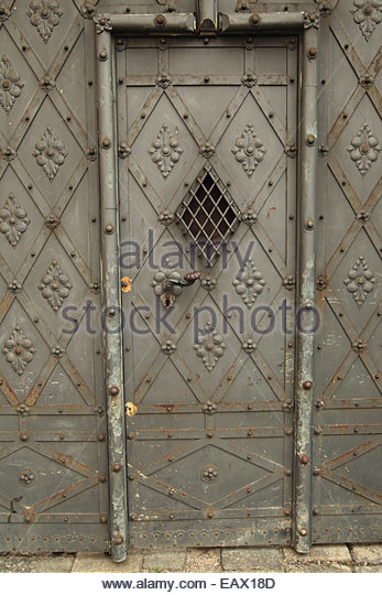A metal door with ornate decoration and a screened window. - Stock Image