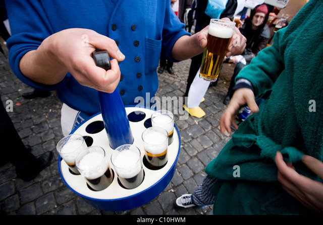 A barman serves Kölsch, typical locar beer, during Carnival Crazy Days in Cologne, Germany. - Stock Image