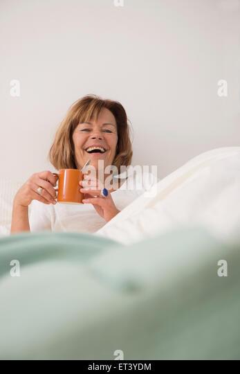 Senior woman at her bedroom drinking tea in the morning, Munich, Bavaria, Germany - Stock-Bilder