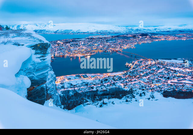 View of the city of Tromso at dusk from the mountain top reached by the Fjellheisen cable car, Troms, Northern Norway - Stock Image