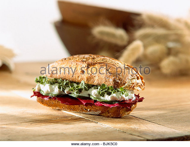 Fresh baked wholemeal bread roll with alfalfa and radish sprouts on ...