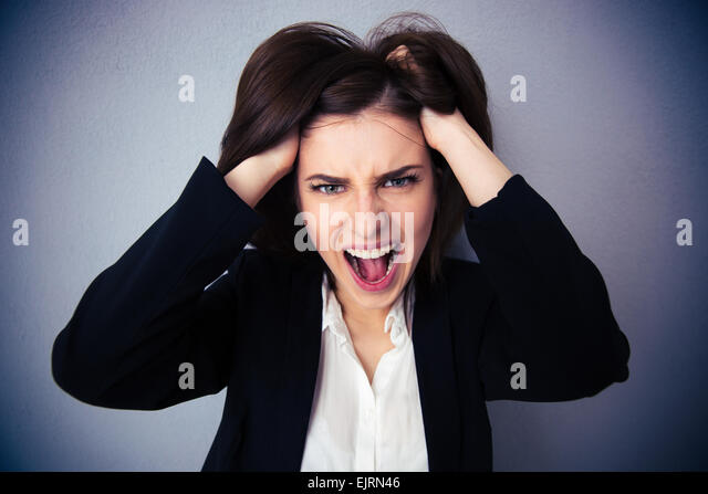 Angry businesswoman shouting over gray background. Holding her hair. Looking at camera - Stock Image