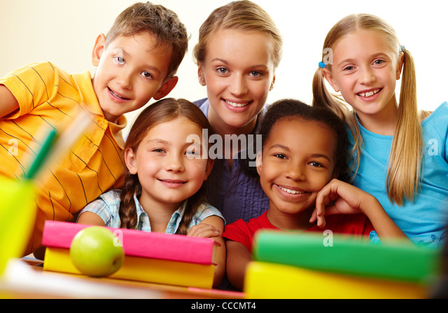 Portrait of smart schoolchildren and their teacher looking at camera in classroom - Stock Image