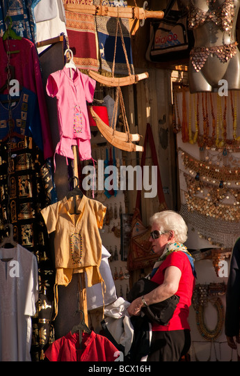 Egypt Kom Ombo village woman tourist red sweater gray hair looking at souvenirs - Stock Image