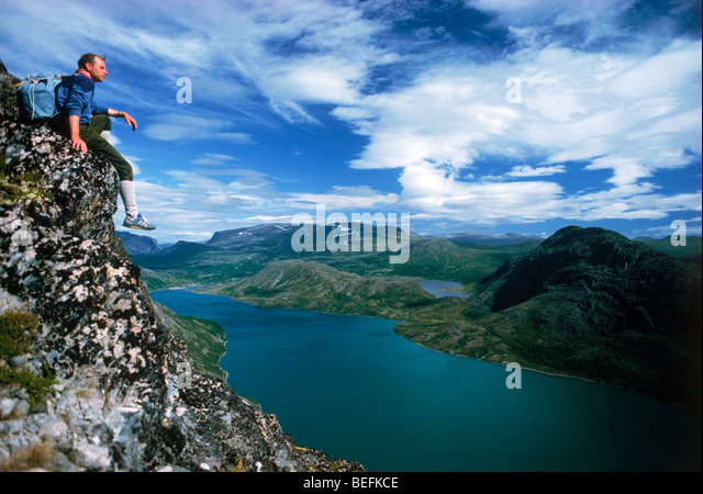 Hiker sitting above Gjende (or Gjendin) Lake in the Jotunheimen mountains in Norway's Jotunheimen National Park - Stock Image