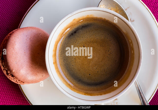 Overhead view of cup of coffee and one French macaroon - Stock Image