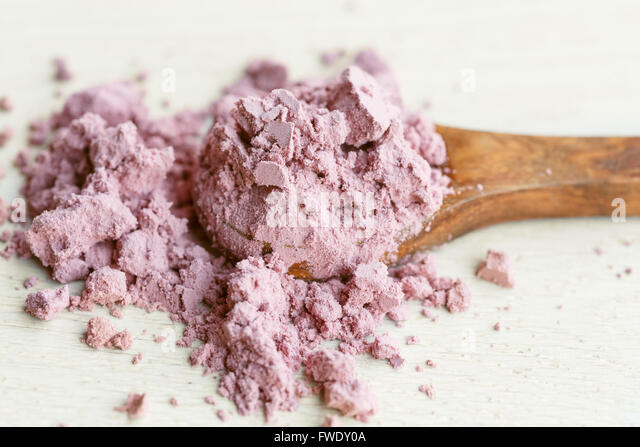 Acai powder on wooden spoon - Stock Image