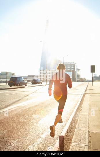 Woman running on city street - Stock-Bilder