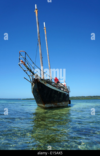 Sailing boat stranded on a shallow reef - Stock Image