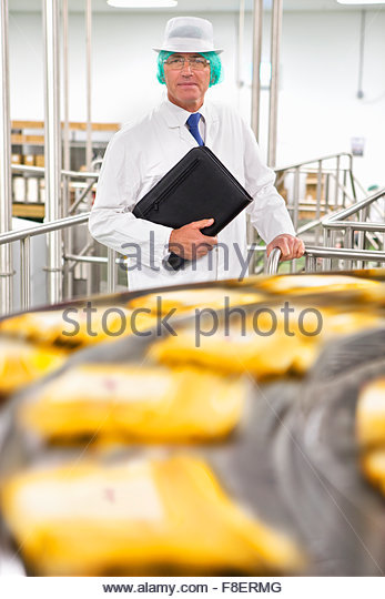 Portrait confident bank manager at production line in cheese processing plant - Stock Image