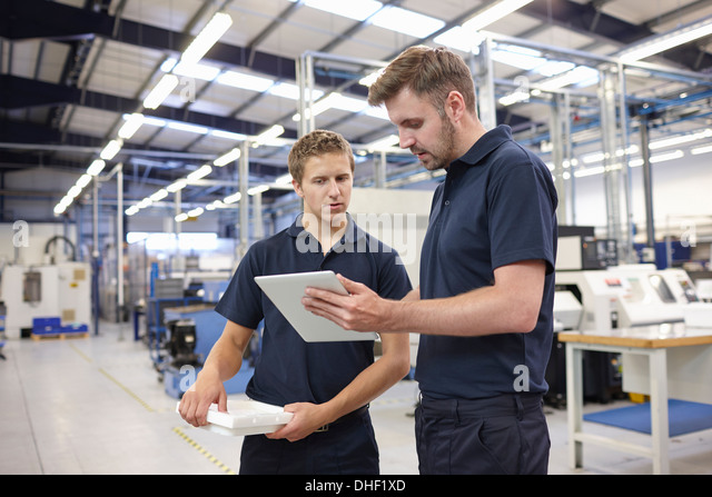 Workers checking order in engineering factory - Stock Image