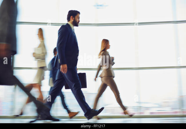 Crowd of modern business people walking down corridor - Stock Image