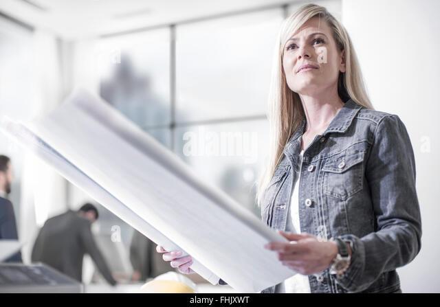 Woman in office holding construction plan - Stock-Bilder