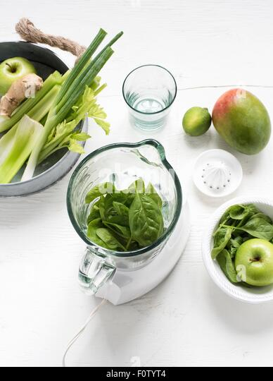 Blender with fresh green fruits and vegetables - Stock Image