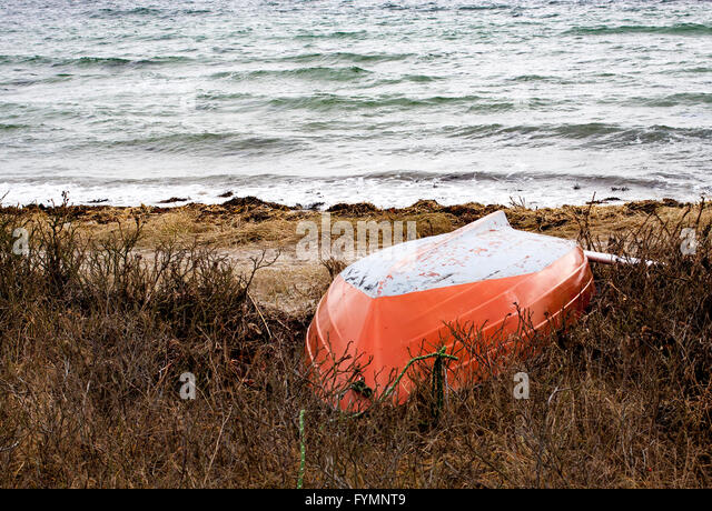 An orange and white rowing Boat lying on the Shore, waiting for summer to come - Stock Image