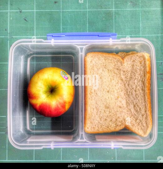 Lunch box with an apple and a sandwich. - Stock Image